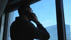 El hombre de negocios acertado joven con una barba hace una llamada en un smartphone en un fondo céntrico Éxito empresarial y almacen de metraje de vídeo