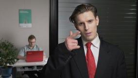 El hombre de negocios acertado joven en la demostración del traje me llama muestra, ligando El hombre trabaja en un ordenador en  almacen de video
