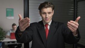 El hombre de negocios acertado joven en el traje que muestra venido aquí firma El hombre trabaja en un ordenador en el fondo 60 f almacen de video