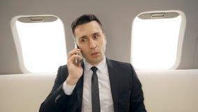 El hombre de negocios acertado joven está hablando en el teléfono que se sienta en interior del aeroplano metrajes