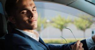 El hombre de negocios acertado joven saca sus gafas de sol y la mirada en la cámara que se sienta dentro del coche Negocio, gente almacen de video