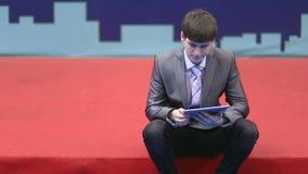 El hombre de negocios acertado trabaja con la tableta almacen de video