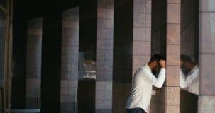 El hombre de negocios africano frustrado en lentes y la camisa blanca está golpeando la pared al aire libre Retrato lateral del p metrajes