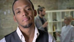 El hombre de negocios africano joven es permanente y mirando en la cámara en oficina, los colegas son que hablan y de consumicion metrajes