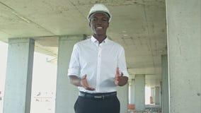 El hombre de negocios africano de risa en la construcción divide la presentación en zonas algo que mira la cámara almacen de metraje de vídeo