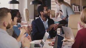 El hombre de negocios afroamericano acertado feliz aplaude las manos así como los colegas, celebrando éxito del equipo en la reun almacen de metraje de vídeo
