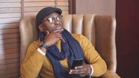 El hombre de negocios afroamericano feliz trabaja en su smartphone que se sienta en una silla cómoda almacen de metraje de vídeo