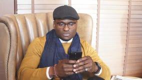 El hombre de negocios afroamericano feliz trabaja en su smartphone que se sienta en una silla cómoda metrajes