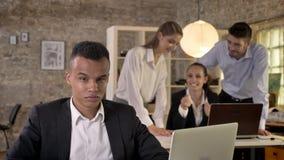 El hombre de negocios afroamericano joven está escuchando cómo sus colegas en fondo cotillean sobre él, concepto del racismo, bul almacen de video