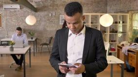 El hombre de negocios afroamericano joven está golpeando ligeramente en la tableta en la oficina, mirando en la cámara, sus coleg metrajes