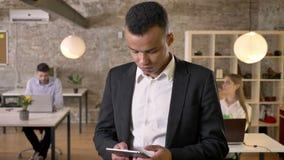 El hombre de negocios afroamericano joven está golpeando ligeramente en la tableta en oficina, sus colegas es establecimiento de  metrajes