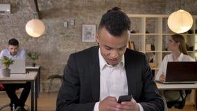 El hombre de negocios afroamericano joven está mecanografiando el mensaje en smartphone en oficina, sus colegas es establecimient metrajes