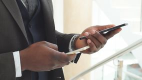 El hombre de negocios afroamericano joven utiliza smartphone Cámara lenta almacen de metraje de vídeo