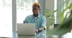 El hombre de negocios afroamericano que usa el ordenador portátil, tiene problema y llama su jefe por el teléfono almacen de video