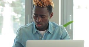 El hombre de negocios afroamericano que usa el ordenador port?til, tiene problema y llama su jefe por el tel?fono almacen de metraje de vídeo