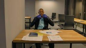 El hombre de negocios afroamericano se sienta con los guantes de boxeo en oficina metrajes