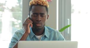 El hombre de negocios afroamericano tiene un problema y llama su jefe por el teléfono, pero el suscriptor no es respuesta almacen de metraje de vídeo