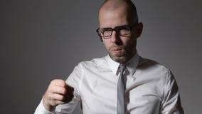 El hombre de negocios amenaza al opositor invisible, mirando la cámara Él parece ser enojado, su finger a la cámara y almacen de video