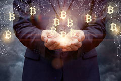 El hombre de negocios apoya bitcoins en sus manos Foto de archivo libre de regalías