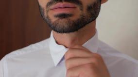 El hombre de negocios ascendente cercano del individuo con la barba en la camisa blanca saca el lazo negro el hombre saca su lazo almacen de metraje de vídeo