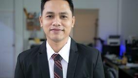El hombre de negocios asiático está sonriendo con felicidad almacen de metraje de vídeo