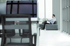 El hombre de negocios asiático joven usando smartphone en el sofá allí es docum fotos de archivo