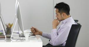 El hombre de negocios asiático se sienta delante de los ordenadores almacen de metraje de vídeo