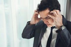 El hombre de negocios asiático tiene dolor de cabeza de la jaqueca de con exceso de trabajo IL Fotos de archivo libres de regalías