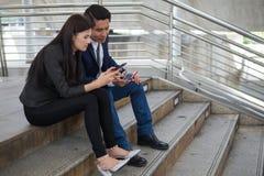 El hombre de negocios asiático y la empresaria que usan el teléfono practican surf Internet y charla con el vendedor para hacer c imágenes de archivo libres de regalías