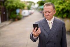 El hombre de negocios asi?tico maduro que usa el tel?fono m?vil en las calles aventaja fotos de archivo libres de regalías