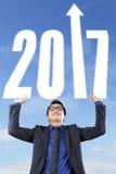 El hombre de negocios aumenta las manos con el número 2017 Imagenes de archivo