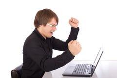 El hombre de negocios aumenta los brazos delante de su ordenador portátil Imagen de archivo libre de regalías