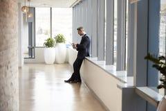 El hombre de negocios Away From Desk en oficina utiliza la tableta de Digitaces Imagen de archivo