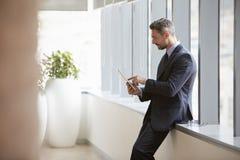 El hombre de negocios Away From Desk en oficina utiliza la tableta de Digitaces Imagenes de archivo