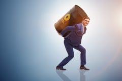 El hombre de negocios bajo carga del barril de aceite Imagen de archivo