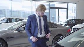 El hombre de negocios barbudo acertado en vidrios y traje de negocios está eligiendo un vehículo en la sala de exposición del coc almacen de video
