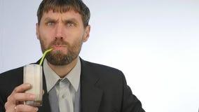 El hombre de negocios barbudo bebe el smoothie del detox, concepto sano de la forma de vida cóctel de la verdura y de la fruta Cá almacen de metraje de vídeo