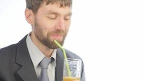 El hombre de negocios barbudo bebe el smoothie del detox, concepto sano de la forma de vida cóctel de la verdura y de la fruta 4K almacen de metraje de vídeo