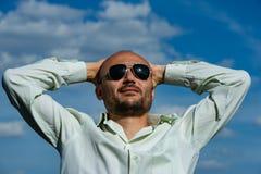 El hombre de negocios barbudo con las gafas de sol dobló sus brazos detrás de su h imagenes de archivo