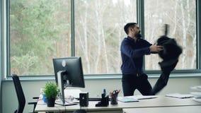 El hombre de negocios barbudo del individuo está expresando el baile positivo de las emociones, está sacando la chaqueta y está l metrajes