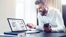 El hombre de negocios barbudo en la camisa blanca se está sentando en la tabla delante del ordenador, mostrando la pluma en la pa fotos de archivo libres de regalías