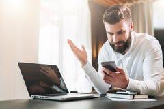 El hombre de negocios barbudo en la camisa blanca se está sentando en la tabla delante del ordenador portátil y está mirando feli fotografía de archivo
