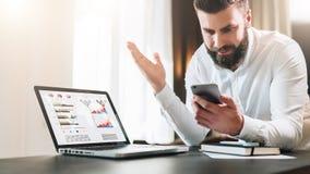 El hombre de negocios barbudo en una camisa blanca se está sentando en una tabla delante de un ordenador portátil con los gráfico foto de archivo