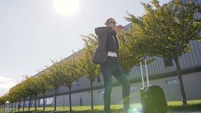 El hombre de negocios barbudo feliz en las lentes vestidas en chaqueta con la maleta es baile, celebrando el logro outdoors metrajes