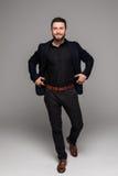 El hombre de negocios barbudo integral en traje negro aisló el fondo gris Fotos de archivo