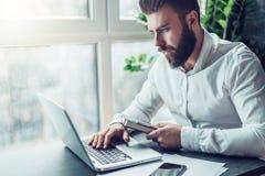 El hombre de negocios barbudo joven en la camisa blanca se está sentando en la tabla y está trabajando en el ordenador portátil E fotografía de archivo