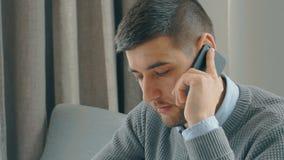 El hombre de negocios barbudo joven está hablando en el teléfono, sentándose en la tabla en café almacen de metraje de vídeo