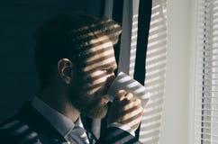 El hombre de negocios barbudo joven hermoso está mirando hacia fuera la ventana Foto de archivo