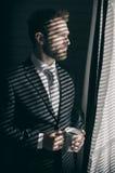 El hombre de negocios barbudo joven hermoso está mirando hacia fuera la ventana Imagen de archivo libre de regalías