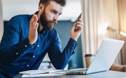 El hombre de negocios barbudo joven se sienta delante del ordenador y mira la pantalla del ordenador portátil con el asombro, aum foto de archivo libre de regalías